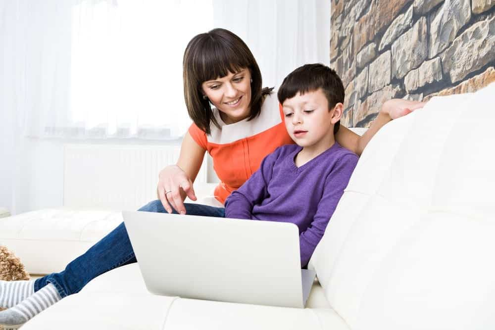 Mom supervising child browsing social media website on laptop