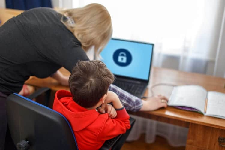 Mom supervising child browsing website on laptop