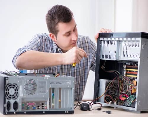 Computer repair technician taking a PC apart