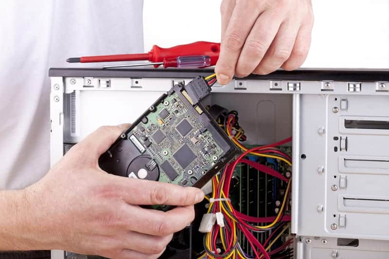 computer technician connecting power to a desktop PC hard drive